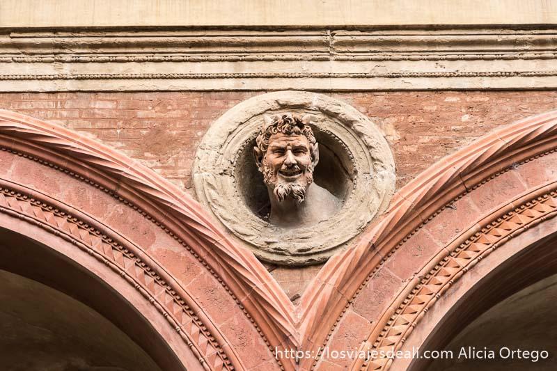 busto del diablo entre dos arcos de una calle del centro de bolonia