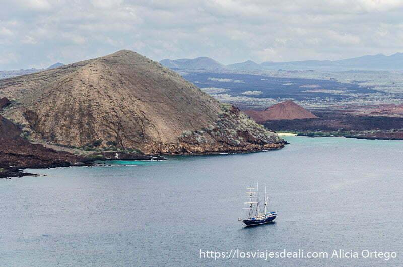 bahía con barco de mástiles y velas y un volcán a la izquierda visto desde isla bartolomé