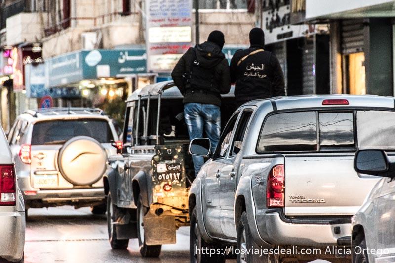 milicianos en una pick up vestidos de negro y con pasamontañas