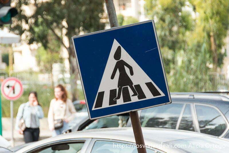 cartel de paso de cebra con una mujer con pañuelo en la cabeza cruzando