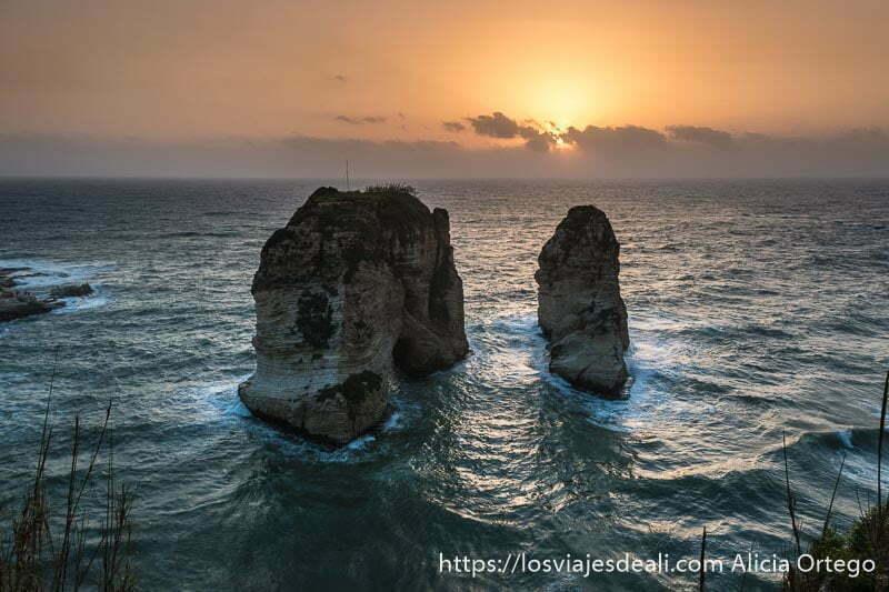 rocas pigeon en el mar con el sol a punto de ponerse en el horizonte