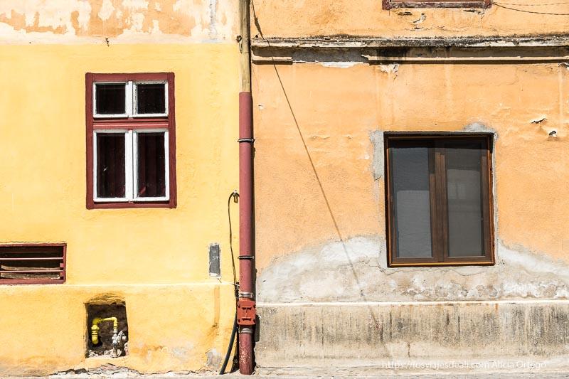 fachada de dos casas separadas por canalón para agua de lluvia una pintada de amarillo y la otra de naranja