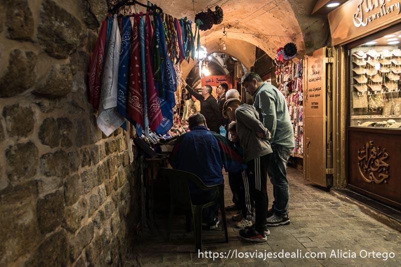 pasillo del zoco con bóvedas una joyería a la derecha y un hombre sentado haciendo algo rodeado por tres niños que miran atentamente