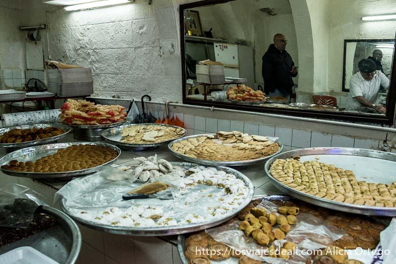 pastelería con grandes bandejas llenas de dulces árabes y un espejo en el que se refleja el pastelero