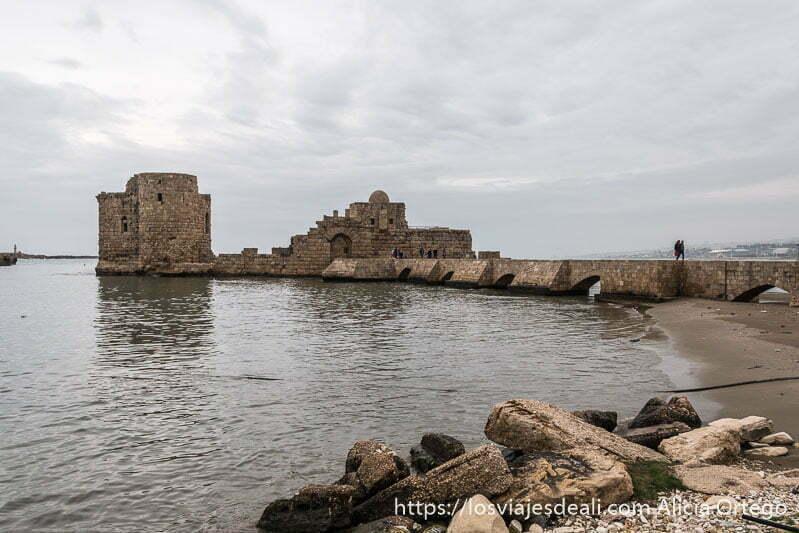 fortaleza de los cruzados con puente de piedra y una pareja andando por él