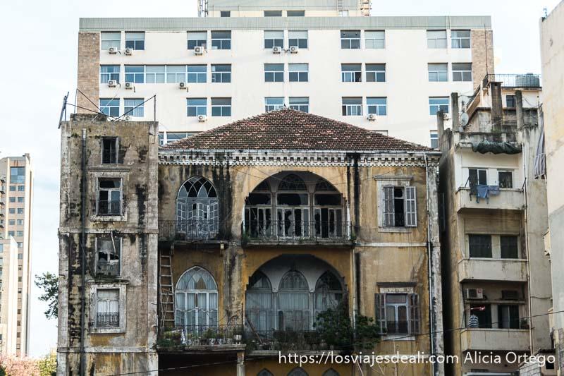 casa antigua medio derruida con grandes balcones y ventanas de cristal rotas y casa nueva más alta detrás