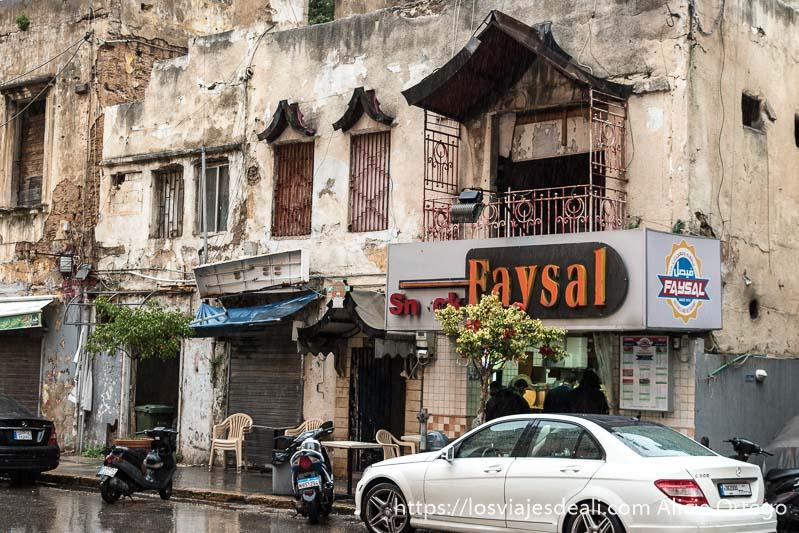 establecimiento de comida rápida en los bajos de edificio antiguo en ruinas