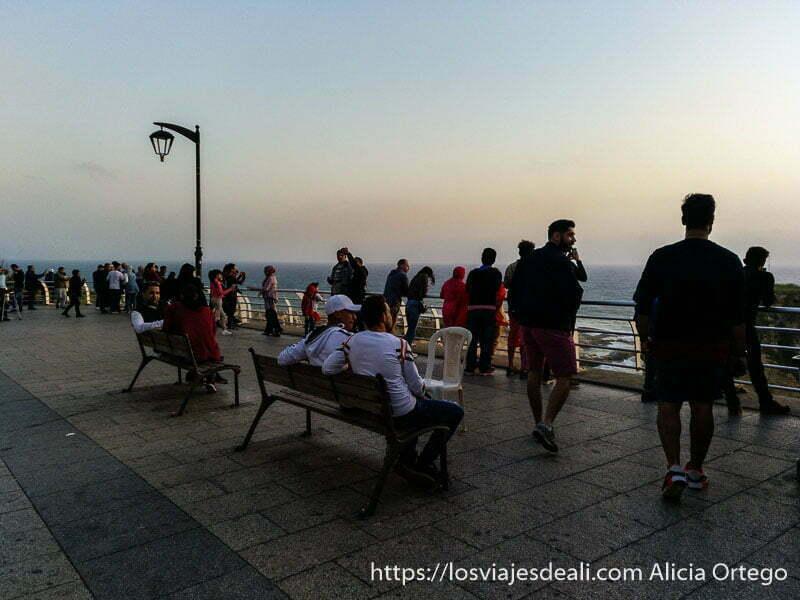 gente asomada a una barandilla viendo el atardecer en el mar