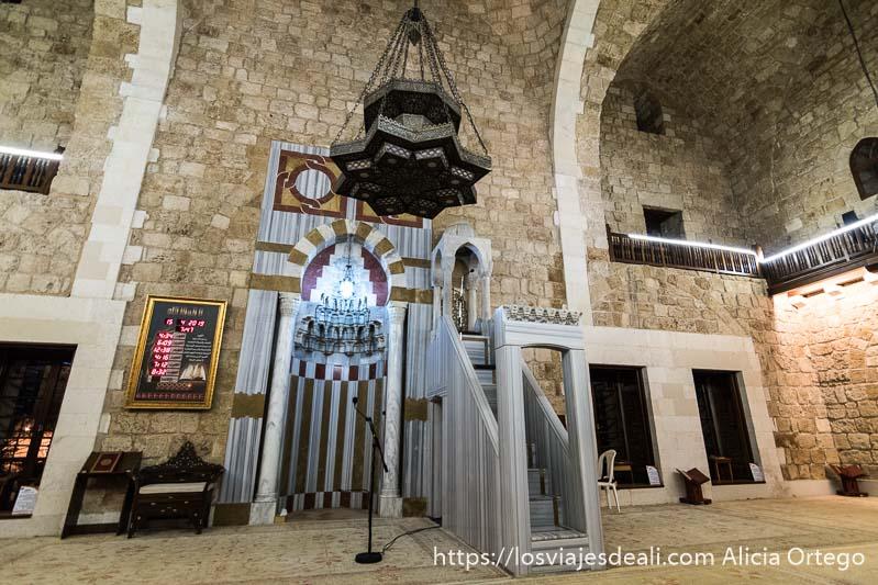interior de mezquita con mirhab de mármol y micrófono
