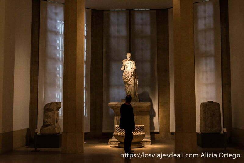 estatua de diosa romana iluminada por luz tenue entre dos columnas y visitante mirándola en el museo nacional de beirut