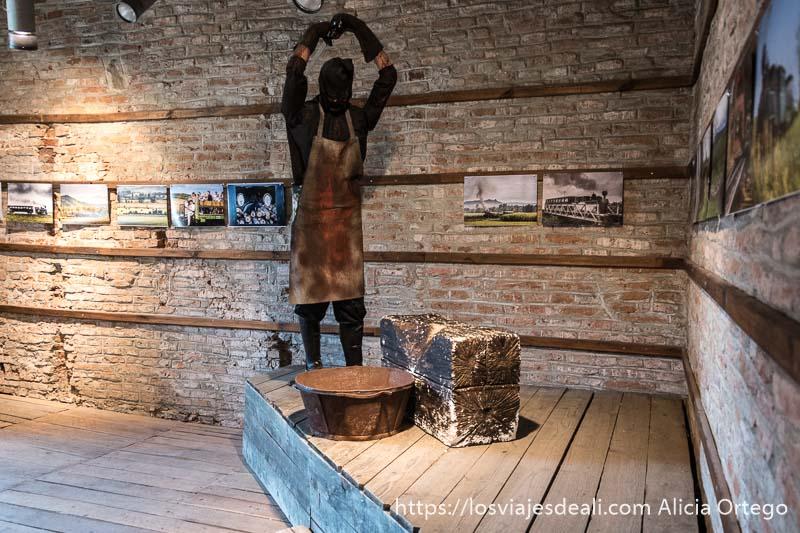 maniquí vestido de verdugo con hacha alzada y tocón de madera delante