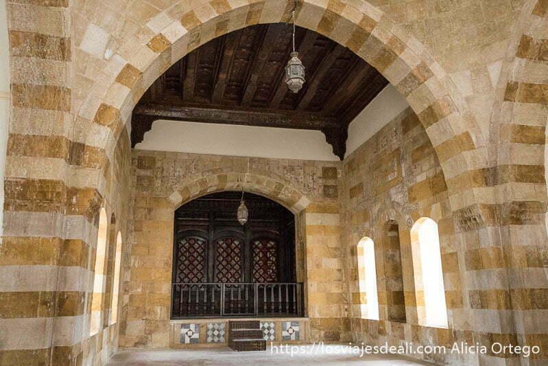 sala de recepción del ayuntamiento de deir el qamar con gran arco y lámparas orientales colgando del techo