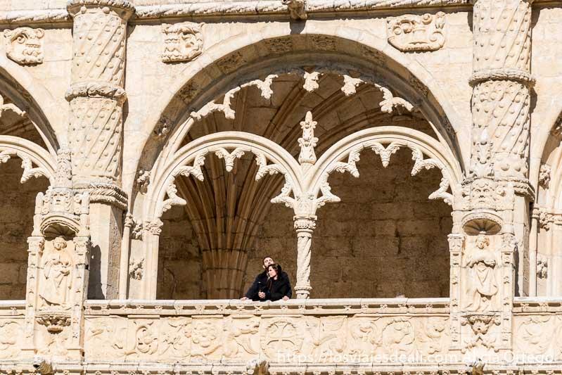 balcón con arcos y mucha decoración en la piedra y una pareja asomada en belem