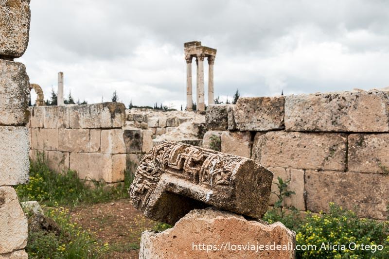 detalle de cornisa con esvástica en relieve en las ruinas de aanjar y al fondo el tetrapilo de cuatro columnas