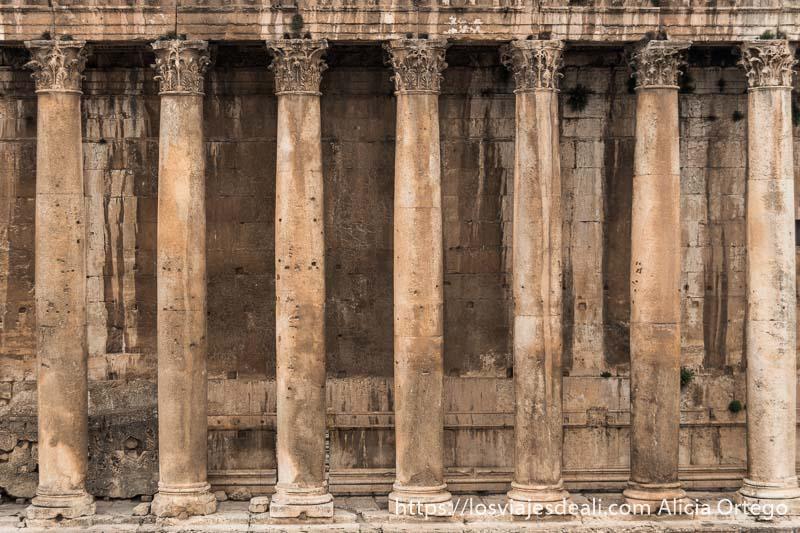 7 columnas con capiteles corintios del templo de baco sosteniendo el techo y detrás muro del templo