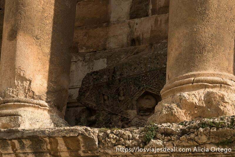 base de dos columnas y en el centro un trozo de techo caído con relieves y figura de sirena