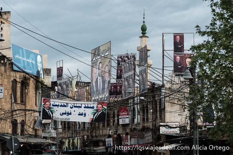 maraña de cables y carteles de candidatos políticos y detrás minarete de mezquita con cielo muy nublado