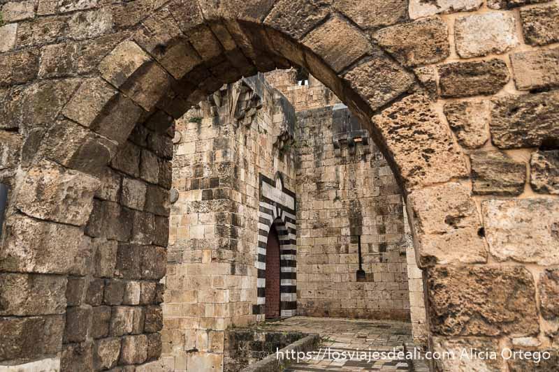 puerta arcada de piedra que da paso al puente para cruzar el foso del castillo de los cruzados de trípoli