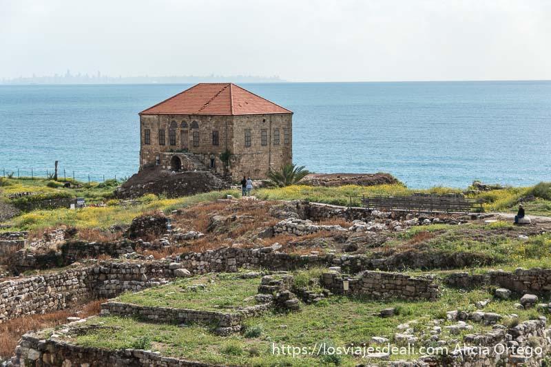 casa de los arquéologos de planta rectangular y dos pisos con ventanas con el mar detrás y el skyline de Beirut al fondo