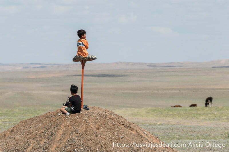 un niño subido a un palo que está en un montón de tierra con las piernas en horizontal como si estuviera sentado y otro niño sentado en el suelo