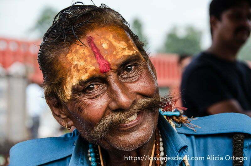 retratos de india hombre con bigote sonriente y con la frente pintada de amarillo y rojo