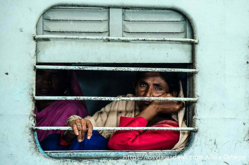 retratos de india mujer mirando por la ventana de un tren con barrotes horizontales