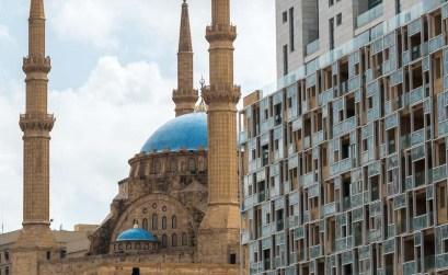 mezquita con cúpulas azules y cuatro minaretes en piedra rojiza junto a edificio de modernos apartamentos en beirut viaje a líbano
