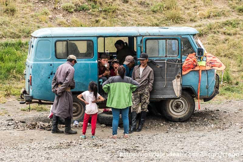 familia mongol en una furgoneta de los años 70 de color azul. A la derecha tienen una cometa de color rojo colgada del retrovisor en el desierto del gobi