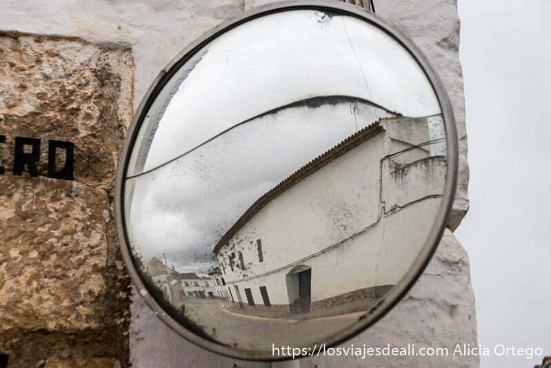 espejo de tráfico donde se refleja una gran casa con paredes blancas en un pueblo de la mancha