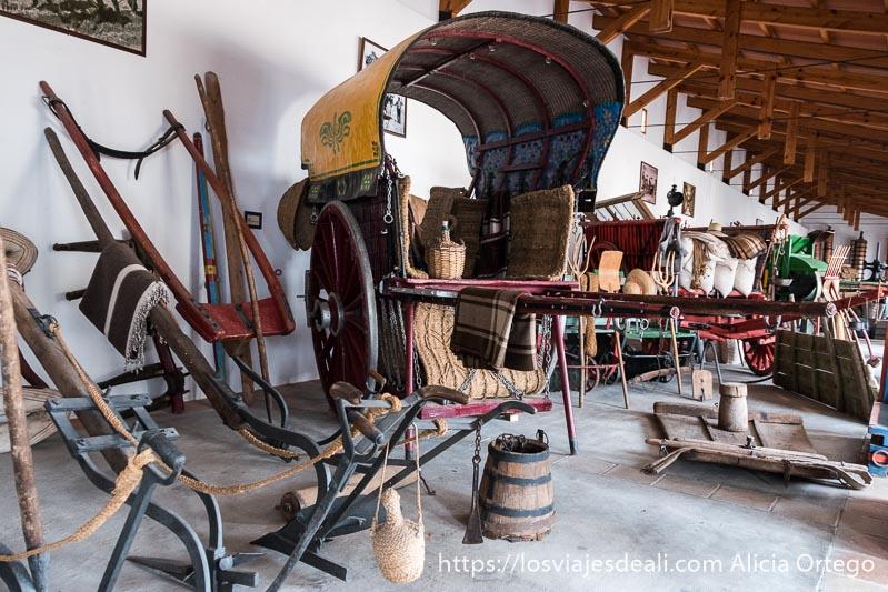 carro antiguo rodeado de arados y otros aperos de labranza en el museo de tomelloso experiencia en la vendimia