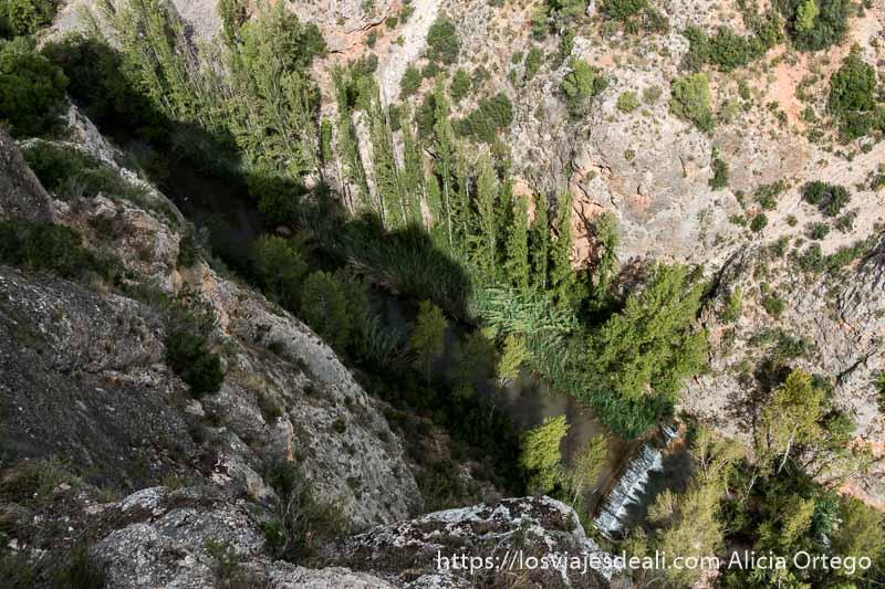 paisaje visto desde arriba de cañón de roca caliza y abajo río con árboles