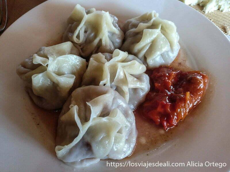 plato de momos unos saquitos de pasta rellenos de carne con salsa en el fondo viajar a mongolia