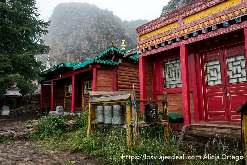edificios de monasterio budista pintados de color rojo verde y amarillo con gran roca detrás semicubierta por niebla en el valle de orkhon
