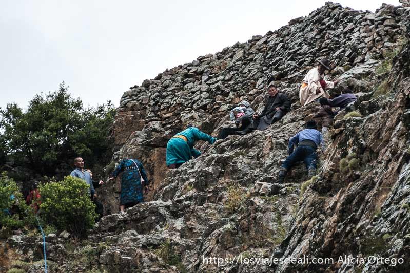 peregrinos trepando por rocas en el monasterio del valle de orkhon