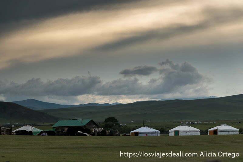 paisaje con tiendas gers y nubes coloreadas por el atardecer