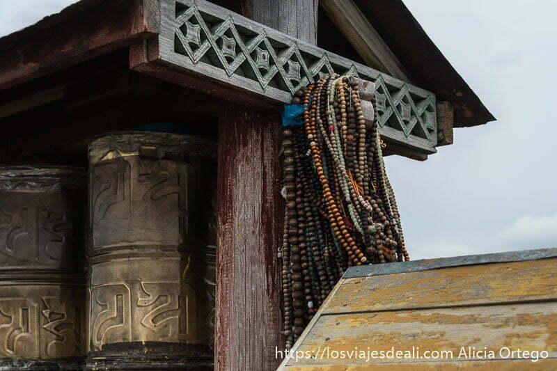 rosarios de bolitas de madera colgados de estructura de madera que cobija molinos de oración tibetanos
