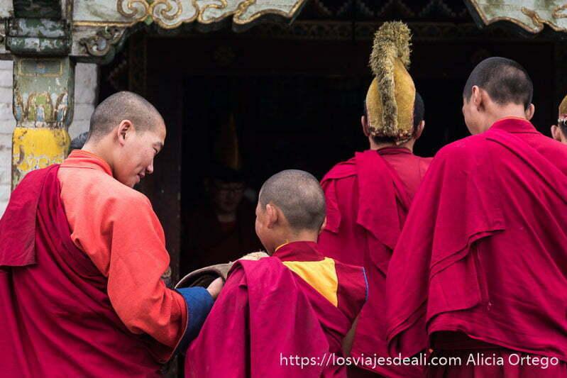 monjes budistas con hábito rojo de espaldas a punto de entrar en el templo tibetano de karakorum