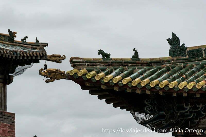 detalle de los tejados con tejas verdes y amarillas y pequeñas estatuas con forma de animales mitológicos en karakorum