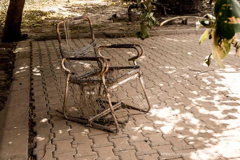 silla muy vieja de metal, oxidada, bajo un árbol