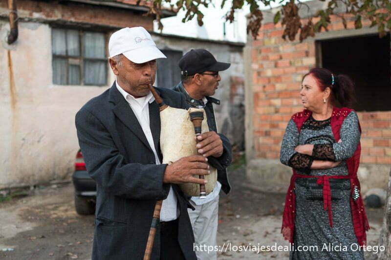 gaitero tocando y detrás tosko con gorra negra hablando con una mujer con chaleco rojo