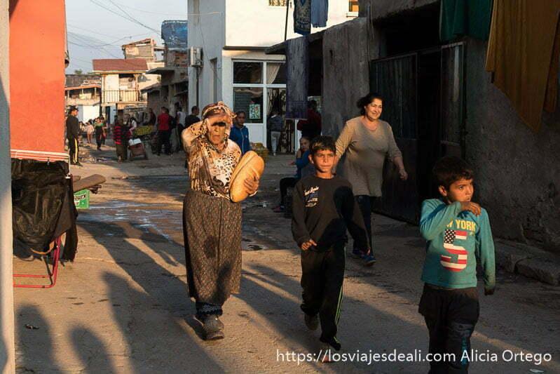 gente andando por la calle en la mahala de sliven una señora mayor con dos panes bajo el brazo gitanos de bulgaria