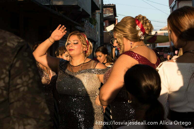 dos mujeres rellenitas con vestidos de fiesta llenos de brillantes y moños de fantasía bailando en la calle en una boda de los gitanos de bulgaria