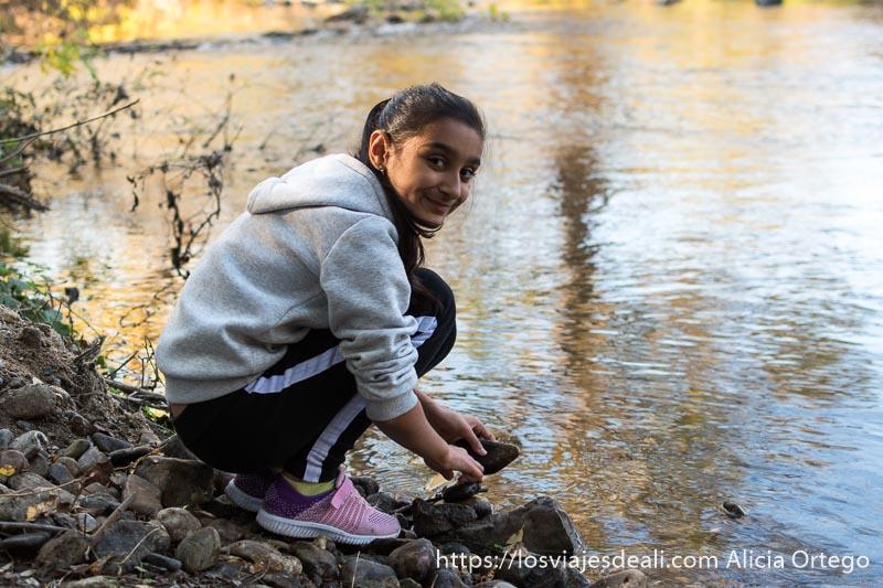 niña gitana agachada en la orilla del río mirando sonriente a la cámara es muy guapa y llena coleta