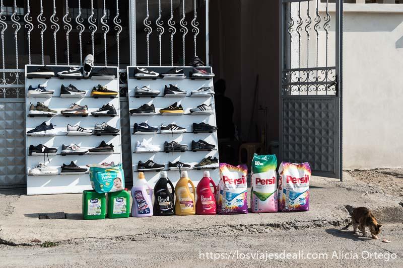 casa con venta de zapatillas de deporte y detergentes y un gato a la derecha comiendo algo en el suelo en el barrio de sliven de los gitanos de bulgaria