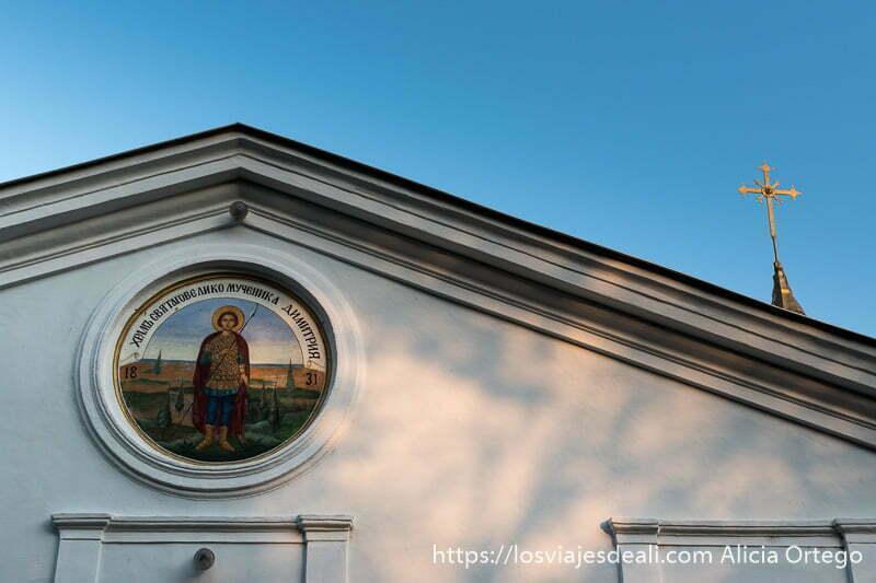 detalle de la fachada de la iglesia de sliven con cruz dorada que se recorta en cielo azul de atardecer y un círculo con el santo pintado