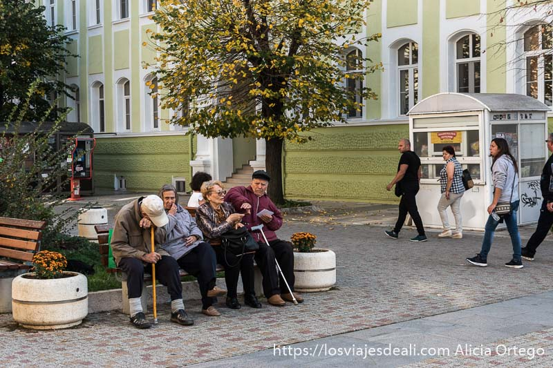 dos hombres y dos mujeres mayores sentados en un banco en el centro de sliven y detrás gran edificio clásico pintado de color verde claro