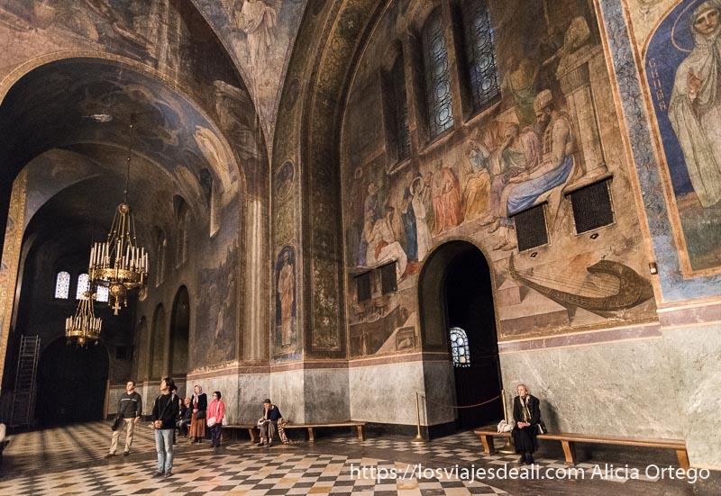 nave lateral de catedral alexander nevski llena de pinturas al fresco y bancos con gente sentada