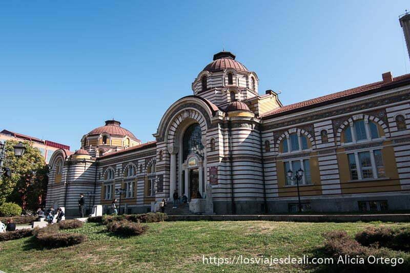 edificio del museo de historia de sofia con puerta con gran arco y cúpula y fachada a dos colores en líneas horizontales