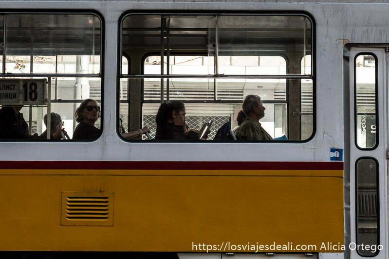 gente sentada en un tranvía amarillo y blanco, mirando por la ventanilla