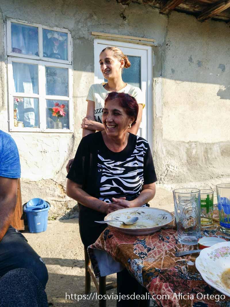 abuela gitana sentada a la mesa con su hija de pie detrás mirando a un lado y sonrientes